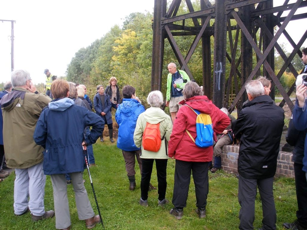 The image shows a group of people on a guided tour under the viaduct. They are being informed of about the design of the viaduct by a guide from the Friends of Bennerley Viaduct.