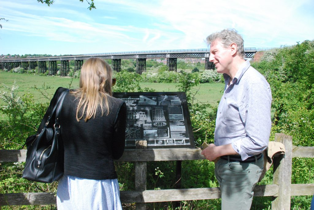 Two officers from the World Monument watch read the interpretation panel at the viaduct viewing point on the Nottingham Canal.