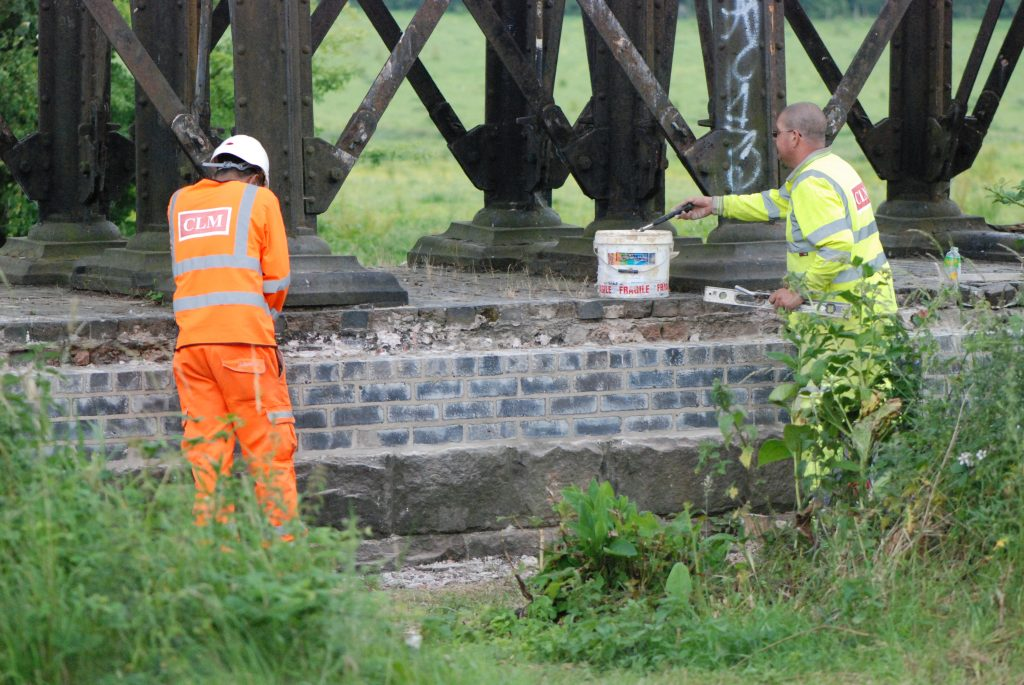 Workmen rebuild one of the crumbling brick pier bases using lime mortar