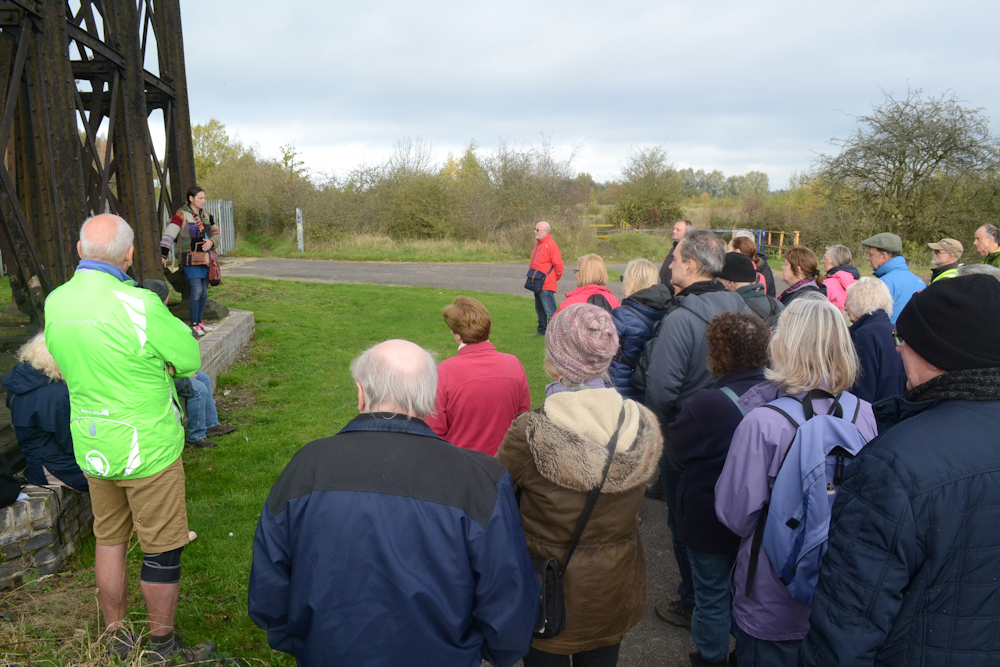 The image shows a civil engineer talking about the design of the viaduct to a group of visitors